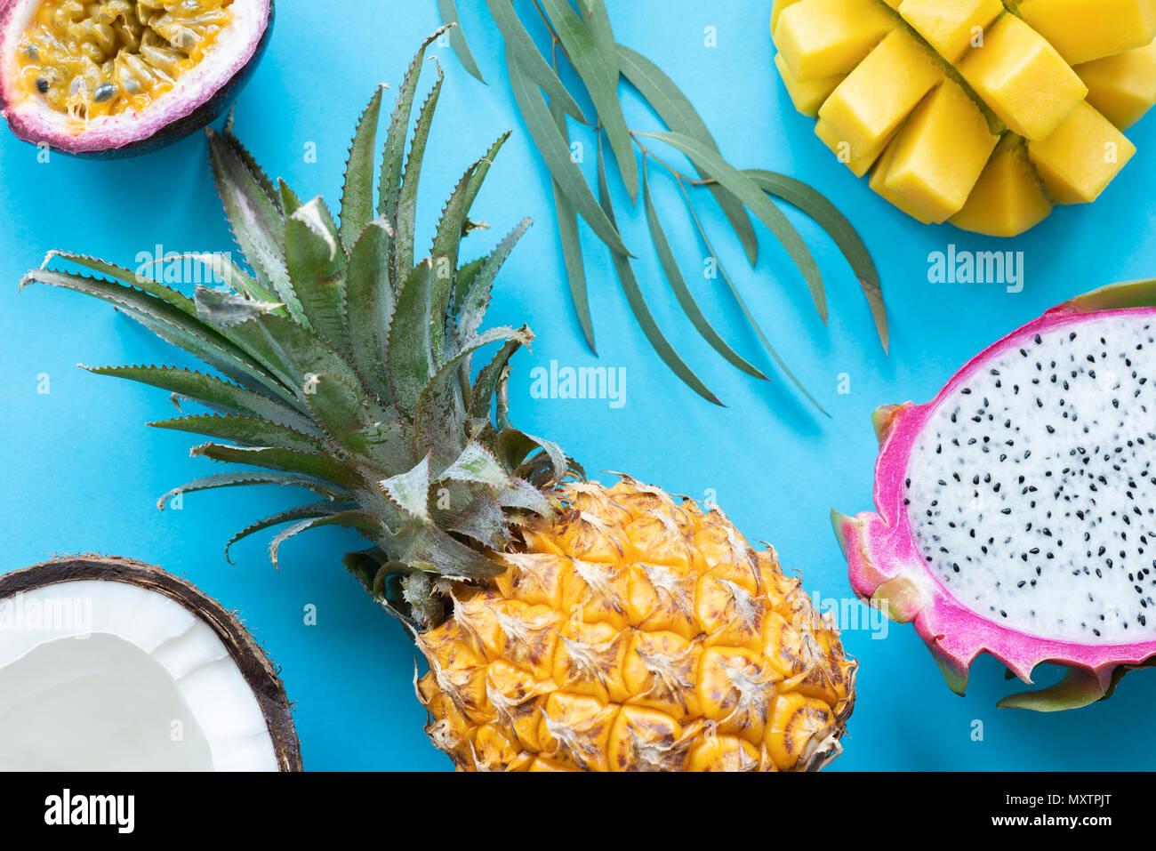 Thai tropical fruits on blue background. Pineapple, mango, pitaya, coconut and passion fruit flat lay - Stock Image