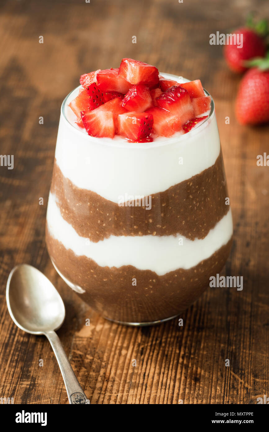 Chia pudding with yogurt, chocolate and strawberries in a glass on wooden table. Closeup view, selective focus - Stock Image