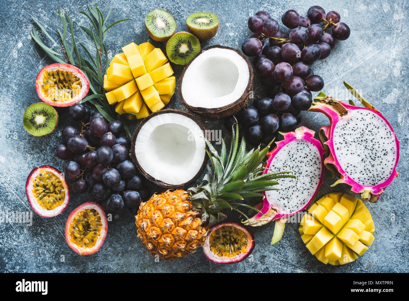 Assortment of exotic tropical fruits, top view. Passionfruit, dragonfruit, mango, pineapple, kiwi, grapes and coconut. Fresh food background. Healthy  - Stock Image