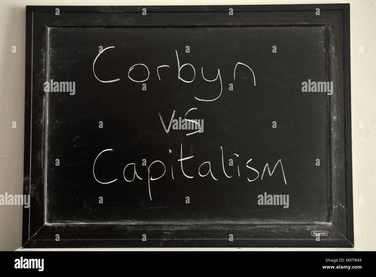 Corbyn vs Capitalism written in white chalk on a blackboard. - Stock Image