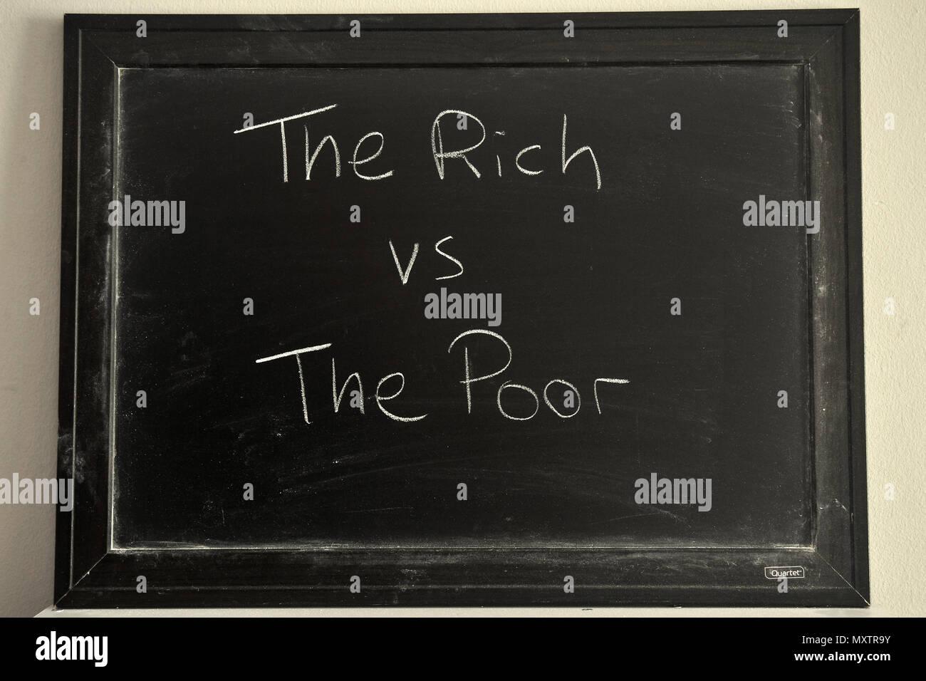 The Rich vs The Poor written in white chalk on a blackboard. - Stock Image