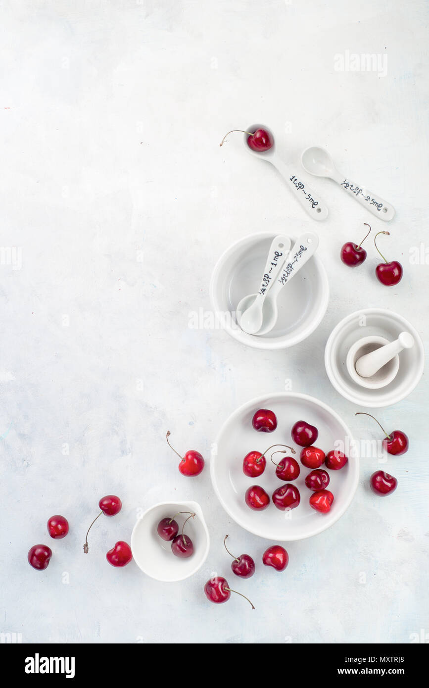 Minimalist cooking concept with red cherries and porcelain baking dishes on a white stone background. White on white flat lay with copy space. - Stock Image