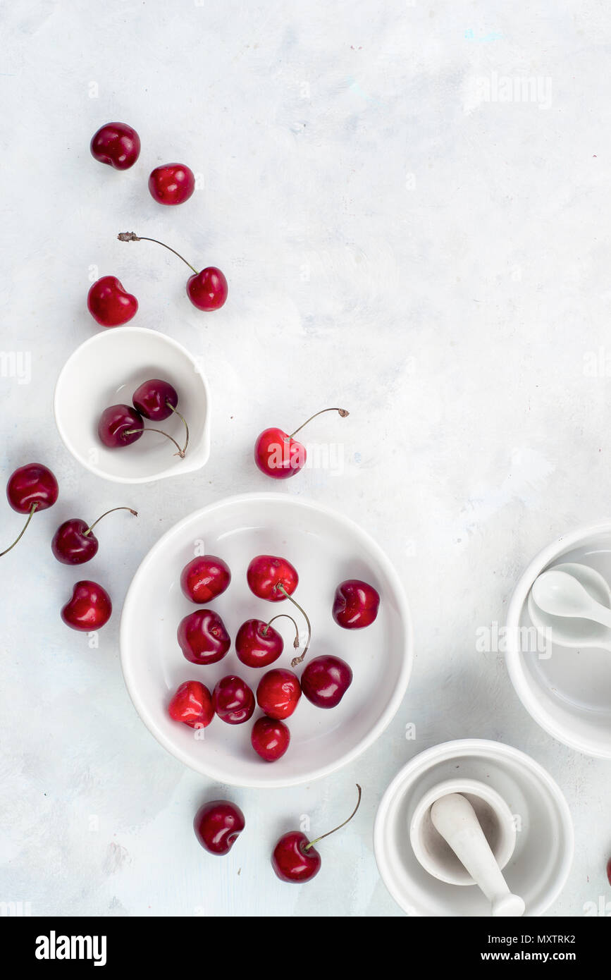 Minimalist cooking concept with red cherries and porcelain baking dishes on a white stone background. White on white flat lay with copy space. Stock Photo