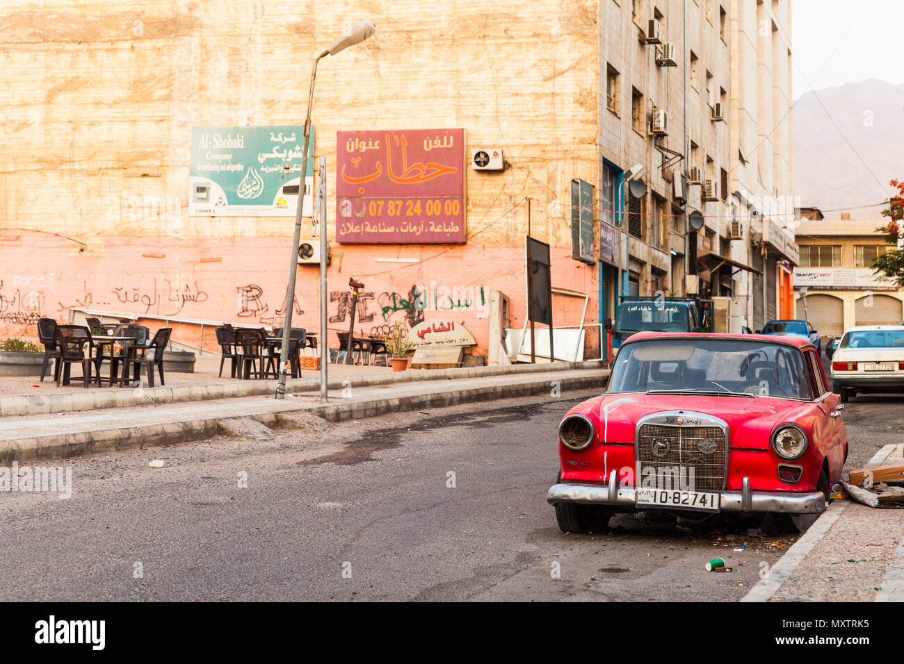 Aqaba, Jordan - May 18, 2018: Red abandoned Mercedes-Benz W110 190, midsize automobile stands on dirty roadside in Aqaba city - Stock Image