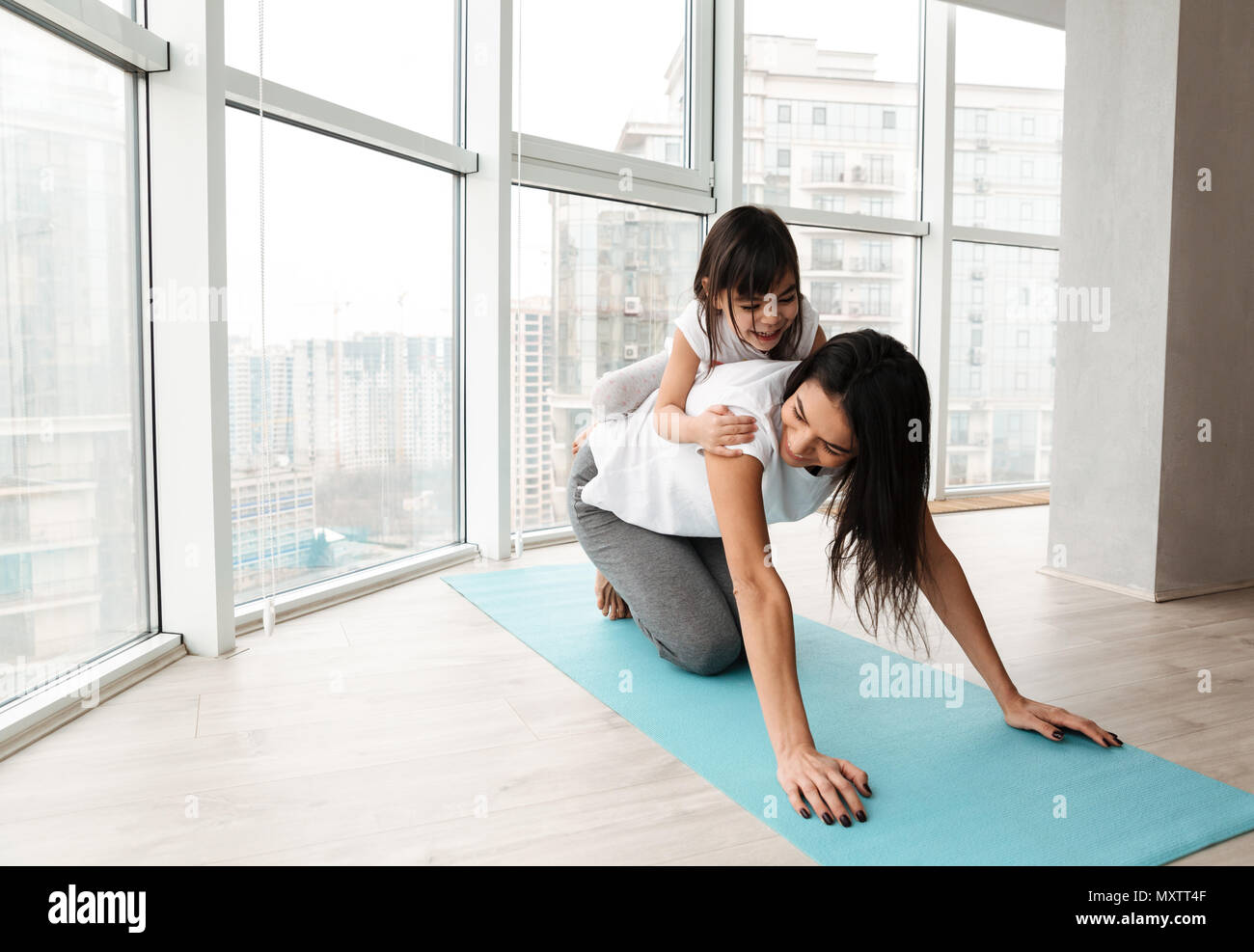 Portrait of gorgeous family mother and child having fun while doing fitness exercises on yoga mat at home - Stock Image