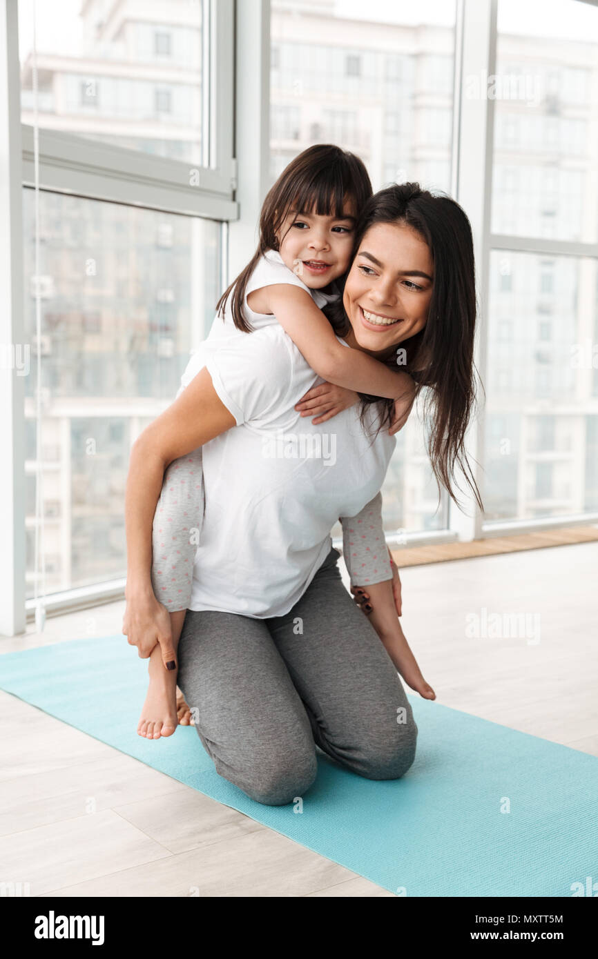 Photo of cheerful family mother and child having fun while woman piggybacking her daughter indoor - Stock Image