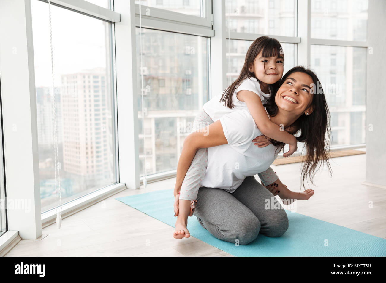 Portrait of gorgeous family mother and child having fun and giving piggyback while doing sports exercises on yoga mat at home - Stock Image
