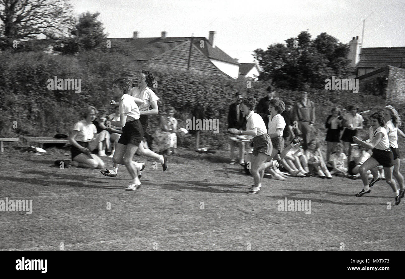 1960, historical picture of secondary schoolgirls taking part in relay race at a inter-school county sports day, Dorset, England, UK. The girl athletes are running up to their teammates to pass them the batons for the next leg of the race. - Stock Image