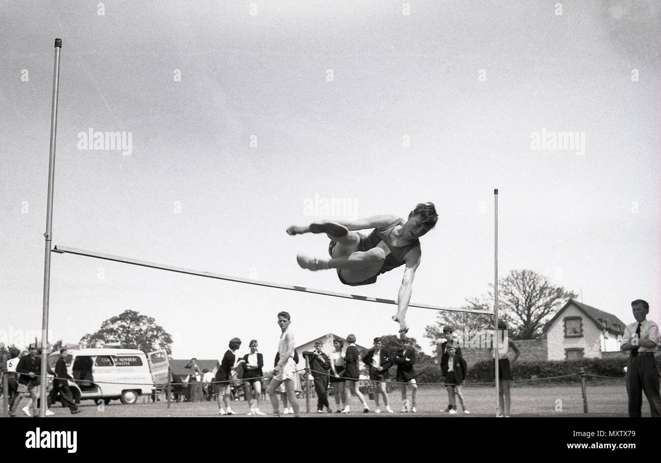 1960, historical picture of secondary schoolboy doing the high jump event at a inter-school county sports day, Dorset, England, UK. - Stock Image