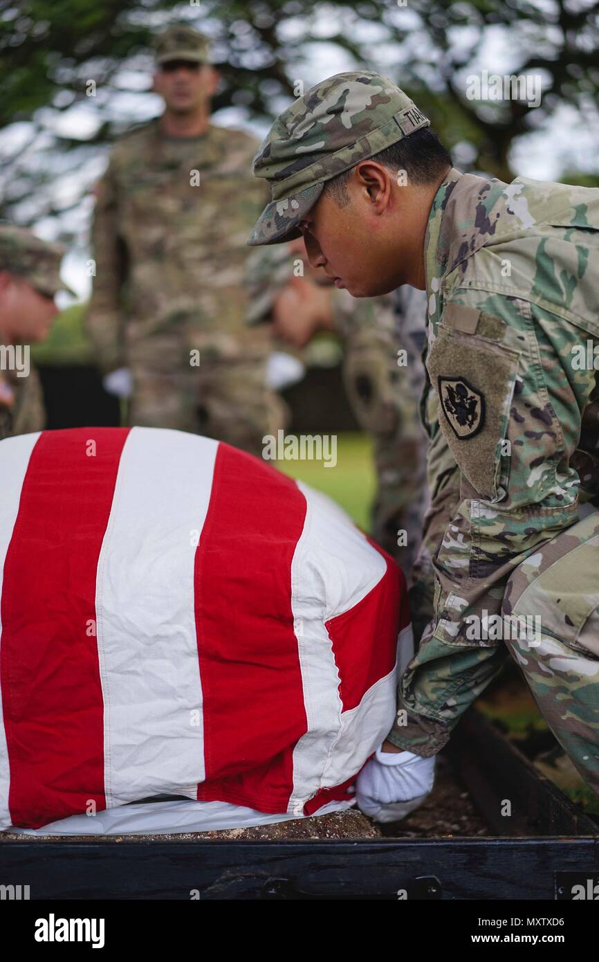 Members of the Defense POW/MIA Accounting Agency (DPAA) honor guard detail drape the American Flag over a disinterred casket during the disinterment ceremony for unknown U.S. Marines from the battle at Tarawa at the National Memorial Cemetery of the Pacific, Honolulu, Hawaii, Nov. 7, 2016. The remains will be transferred to the DPAA laboratory for identification. DPAA's mission is to provide the fullest possible accounting for our missing personnel to their families and the nation. (U.S. Army photo by Sgt. Jose H. Rodriguez Guzman/DPAA) Stock Photo