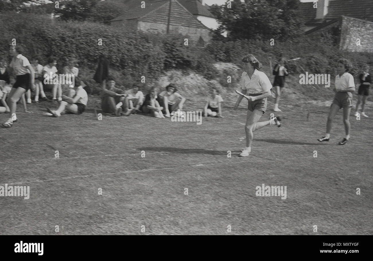 1960, historical picture of secondary schoolgirls taking part in a relay race in a inter-school county sports day, Dorset, England, UK. One of the girls is shown carrying the relay baton in her left hand while running as fast as she can on the grass track. - Stock Image