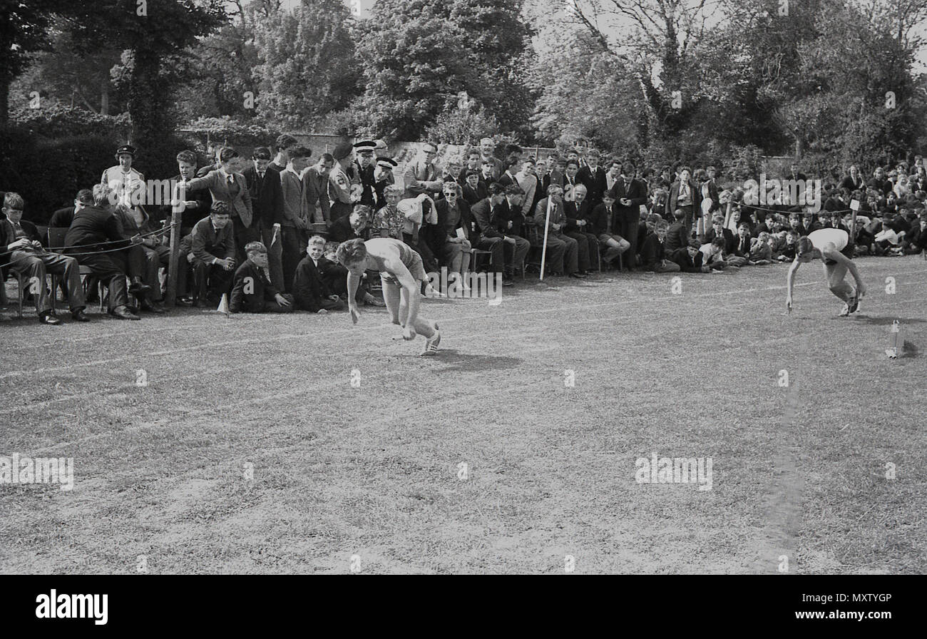 1960, historical picture of secondary school children taking part in a inter-school county sports day, Dorset, England, UK. Here we see two  boys crouching down in position about to start a race on a grass track, with watching spectators close by. Stock Photo
