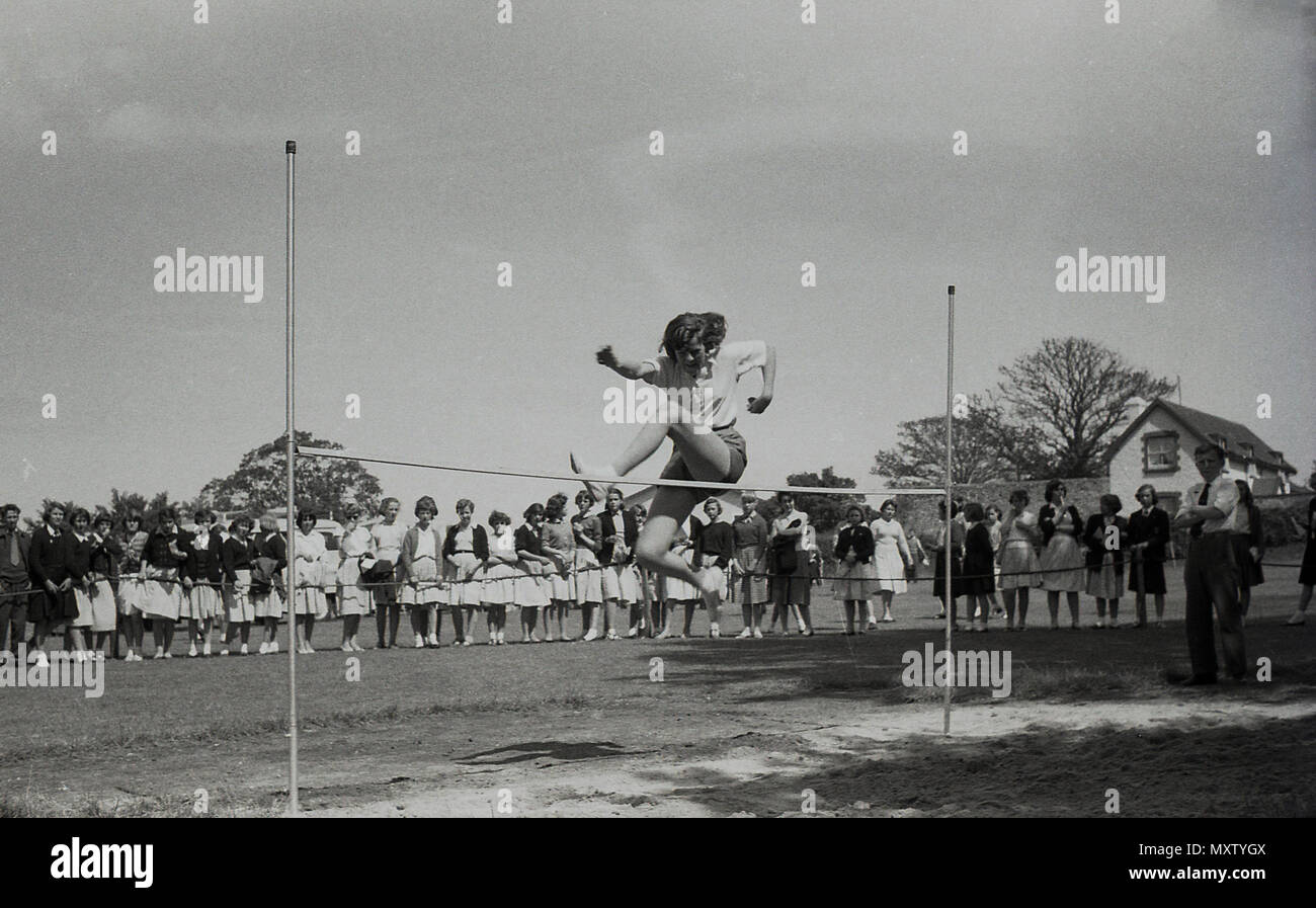 1960, historical picture of secondary schoogirl taking part in an inter-school county sports day, Dorset, England, UK. Here we see her doing the high jump with a rather individual style watched by a line of spectatotrs. - Stock Image