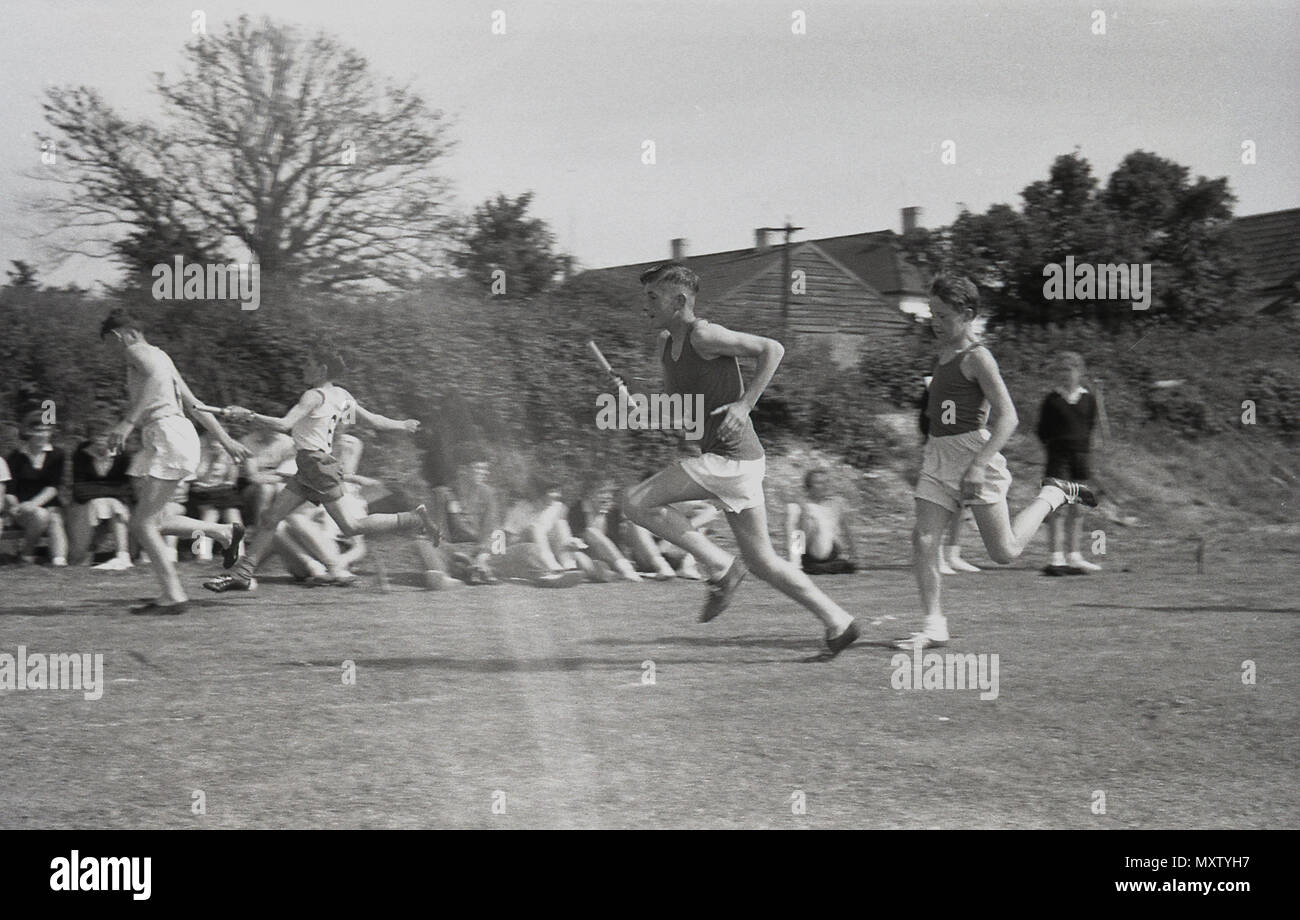 1960, historical picture, secondary schoolboys taking part in an inter-school county sports day, Dorset, England, UK. Here we see them competing in a team relay race on a grass track, as the runners pass the baton to their teammate for the next leg of the race. - Stock Image