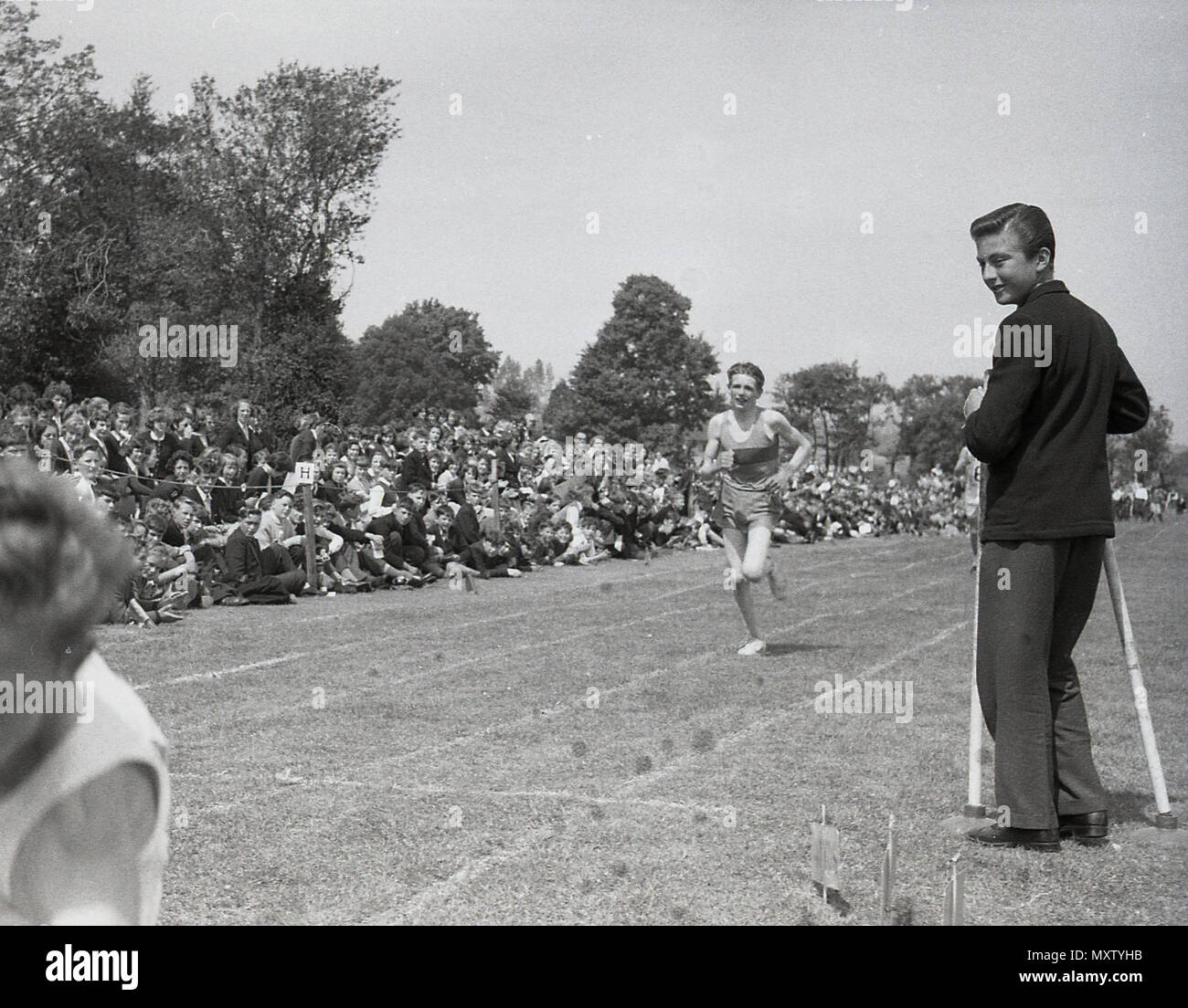 1960, historical picture of secondary school boys taking part in a running race at an inter-school county sports day, Dorset, England, UK. The winner of this grass track race appears to be falling down after the finishing line. - Stock Image
