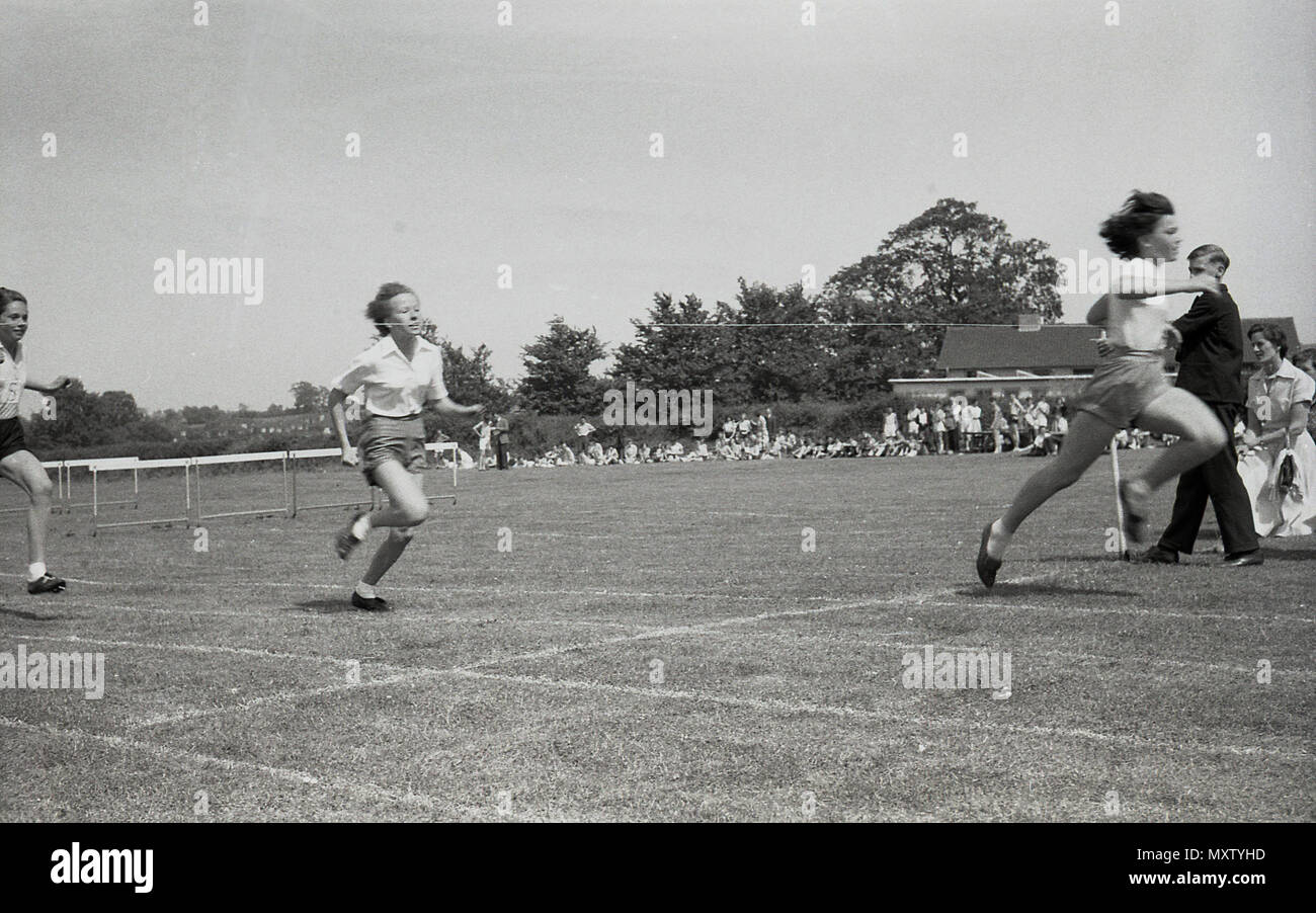 1960, historical picture of secondary school children taking part in a inter-school county sports day, Dorset, England, UK. We see here young girls taking part in a running race, with the girl on the right the first to hit the winning tape. - Stock Image