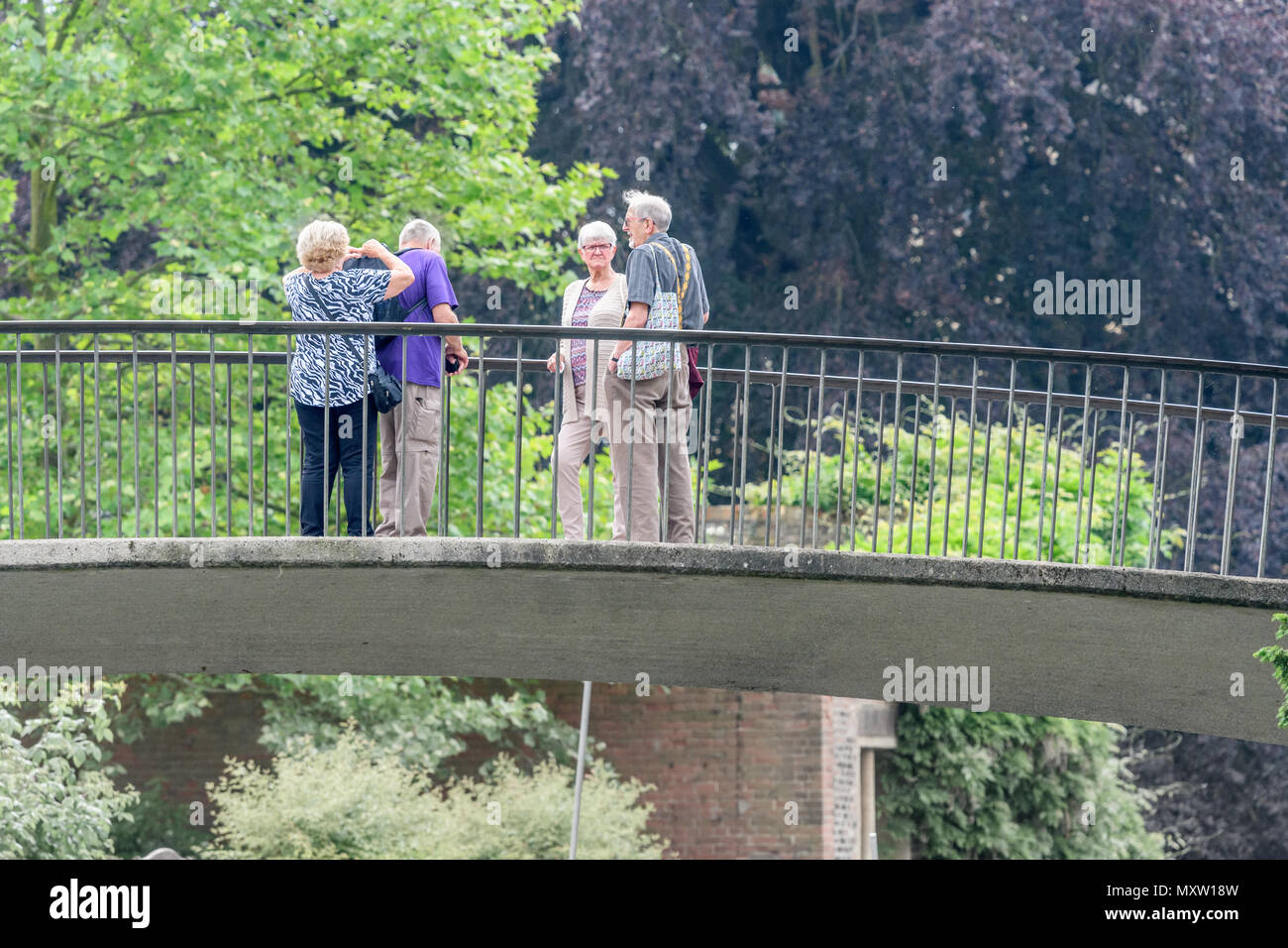 A pair of retired couples on Garret Hostel lane bridge over the river Cam at Trinity Hall college, university of Cambridge, England, on a sunny summer - Stock Image