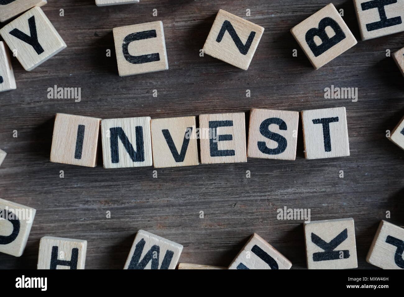 Word 'INVEST' on cube dice on wood table - Stock Image