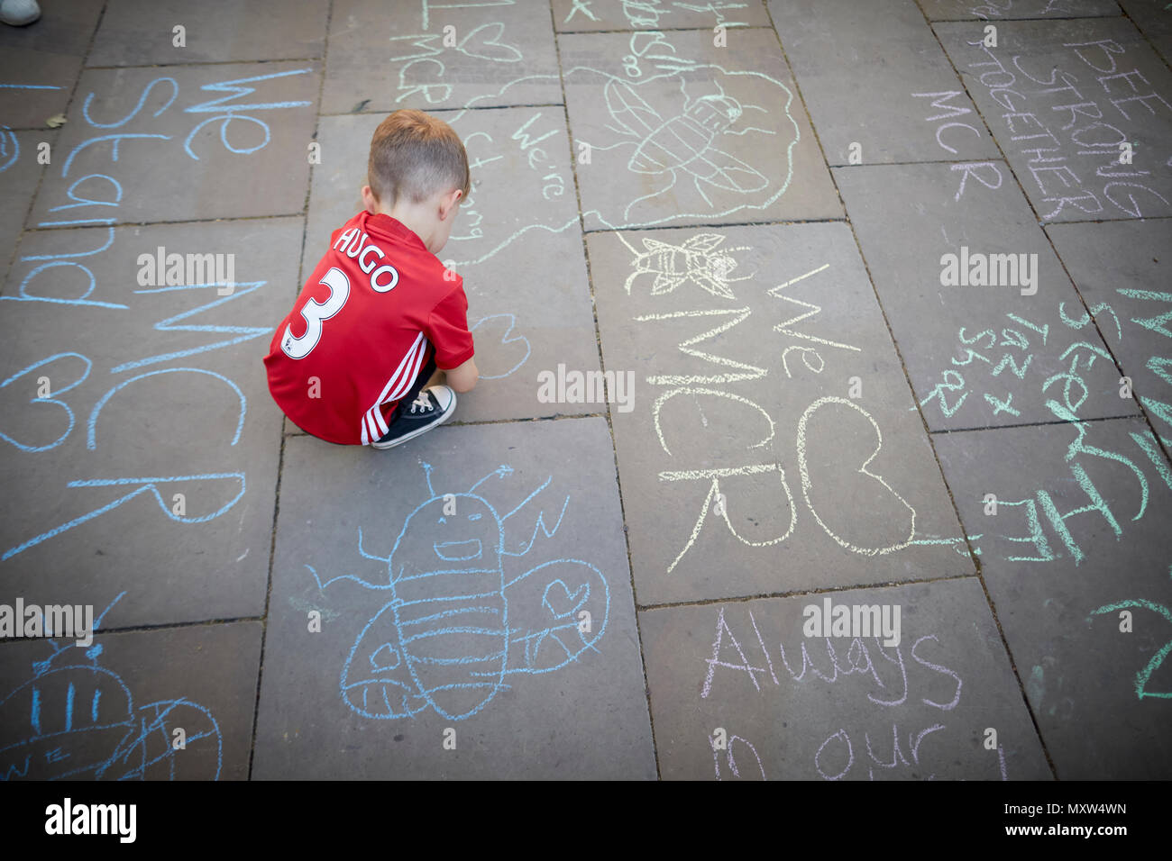 Manchester Arena terror attack 1 year anniversary A little boy drawing on the floor in St Ann's Square, Manchester - Stock Image