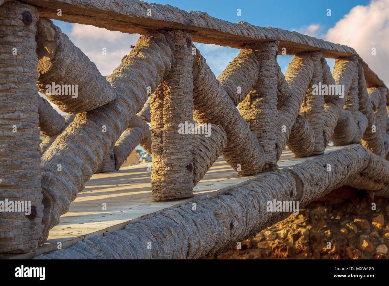Wooden fence made of palm trunks with partly cloudy sky in sunrise time at Montaza public park in summer time, Alexandria, Egypt - Stock Image
