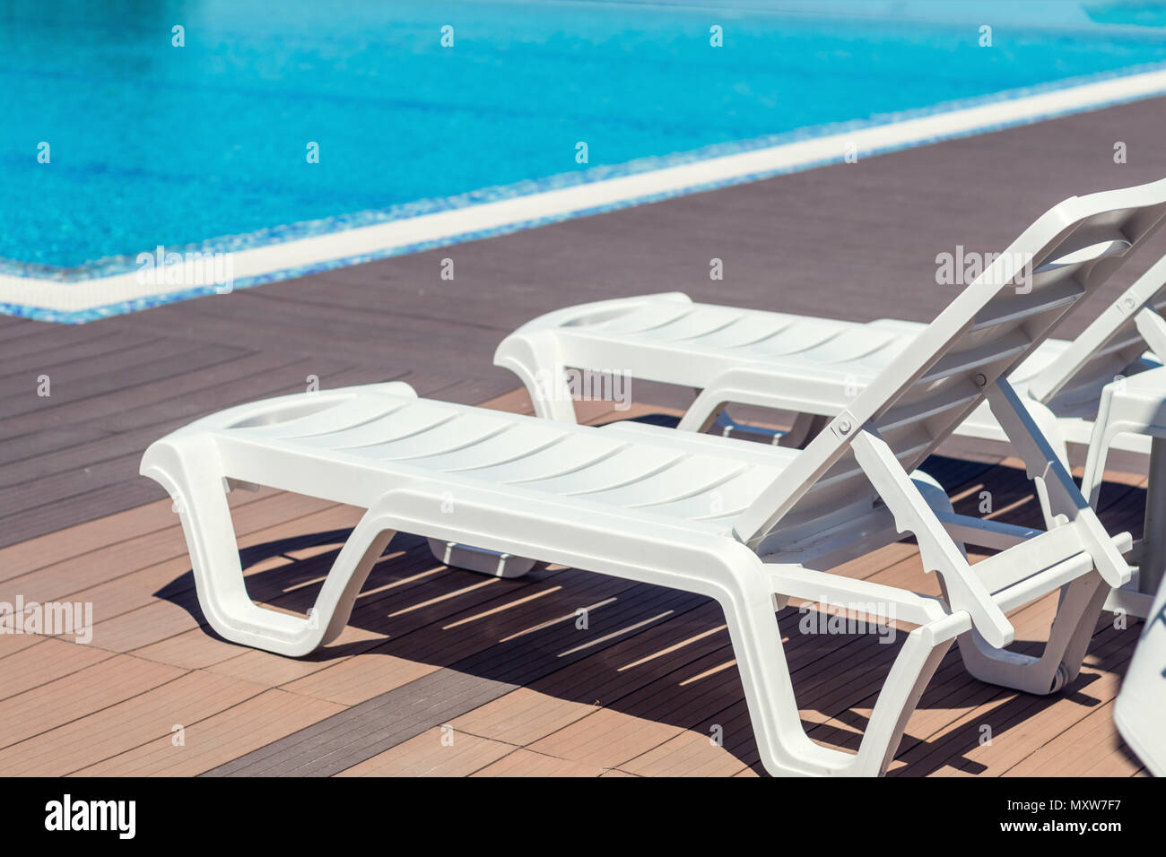 Swimming pool with wooden deck at hotel.Summer sunny day. Lounge ...