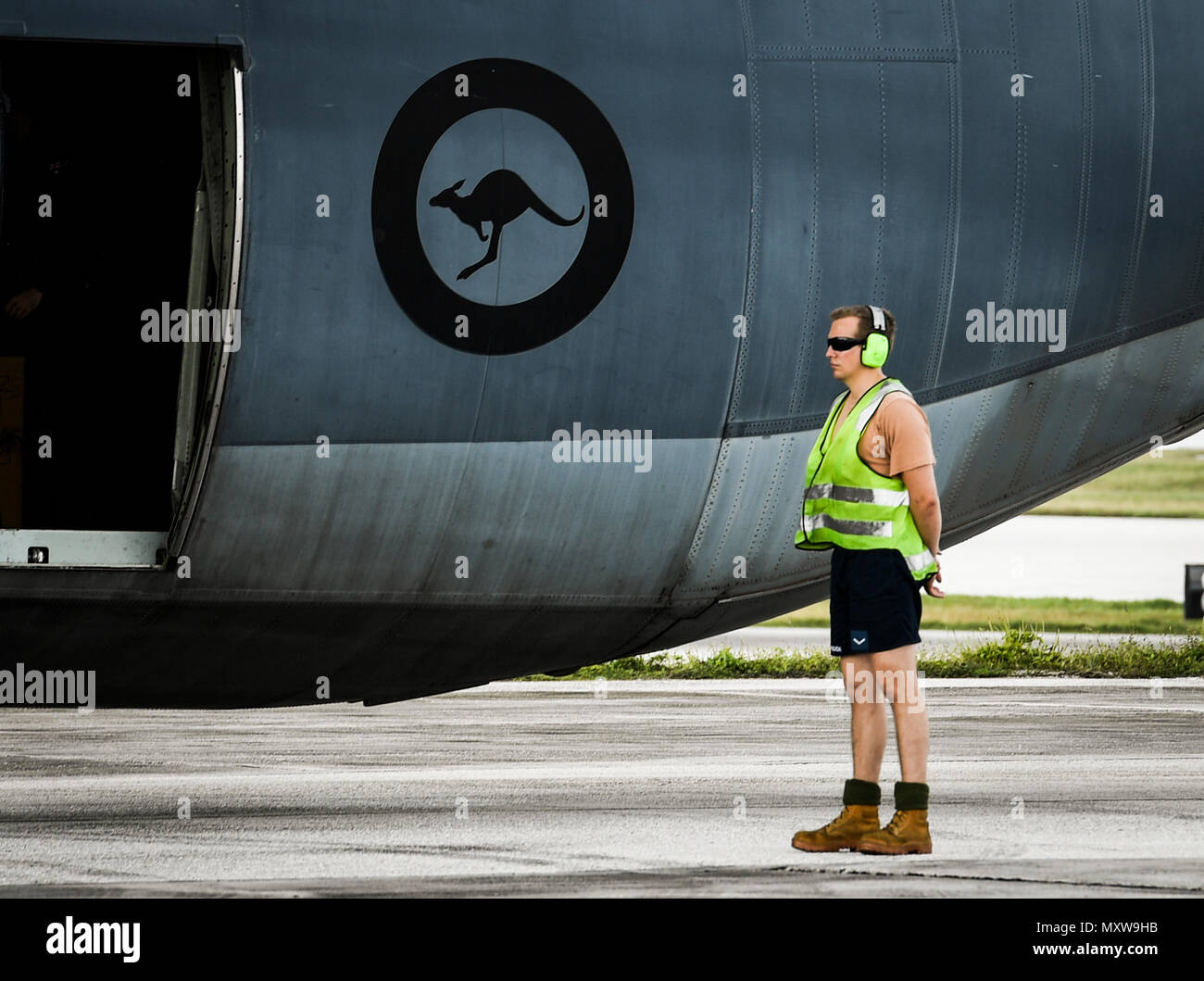 A maintainer with the Royal Australian Air Force waits to marshal a C-130J Super Hercules for takeoff during Operation Christmas Drop at Andersen Air Force Base, Guam, Dec. 7, 2016. The RAAF sent a C-130J to OCD to train with the 36th Airlift Squadron and the Japan Self Defense Force, helping participants understand each other's techniques and giving them a chance to offer each other insight. Bilateral training improves participants's abilities to work together during real world scenarios, such as delivering disaster relief supplies.(U.S. Air Force photo by Senior Airman Elizabeth Baker/Releas - Stock Image