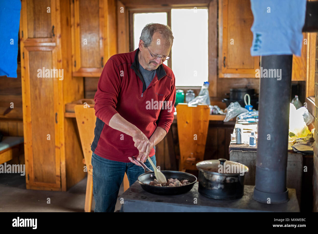 Ontonagon, Michigan - John West cooks dinner on a wood stove in a backpackers' cabin in Porcupine Mountains Wilderness State Park. The park maintains  Stock Photo