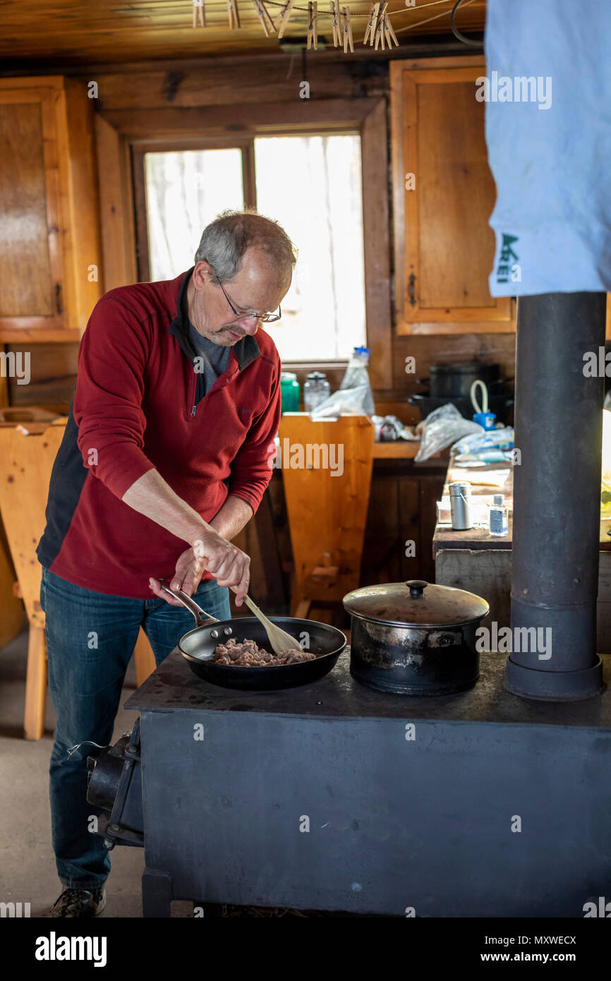 Ontonagon, Michigan - John West cooks dinner on a wood stove in a backpackers' cabin in Porcupine Mountains Wilderness State Park. The park maintains  - Stock Image