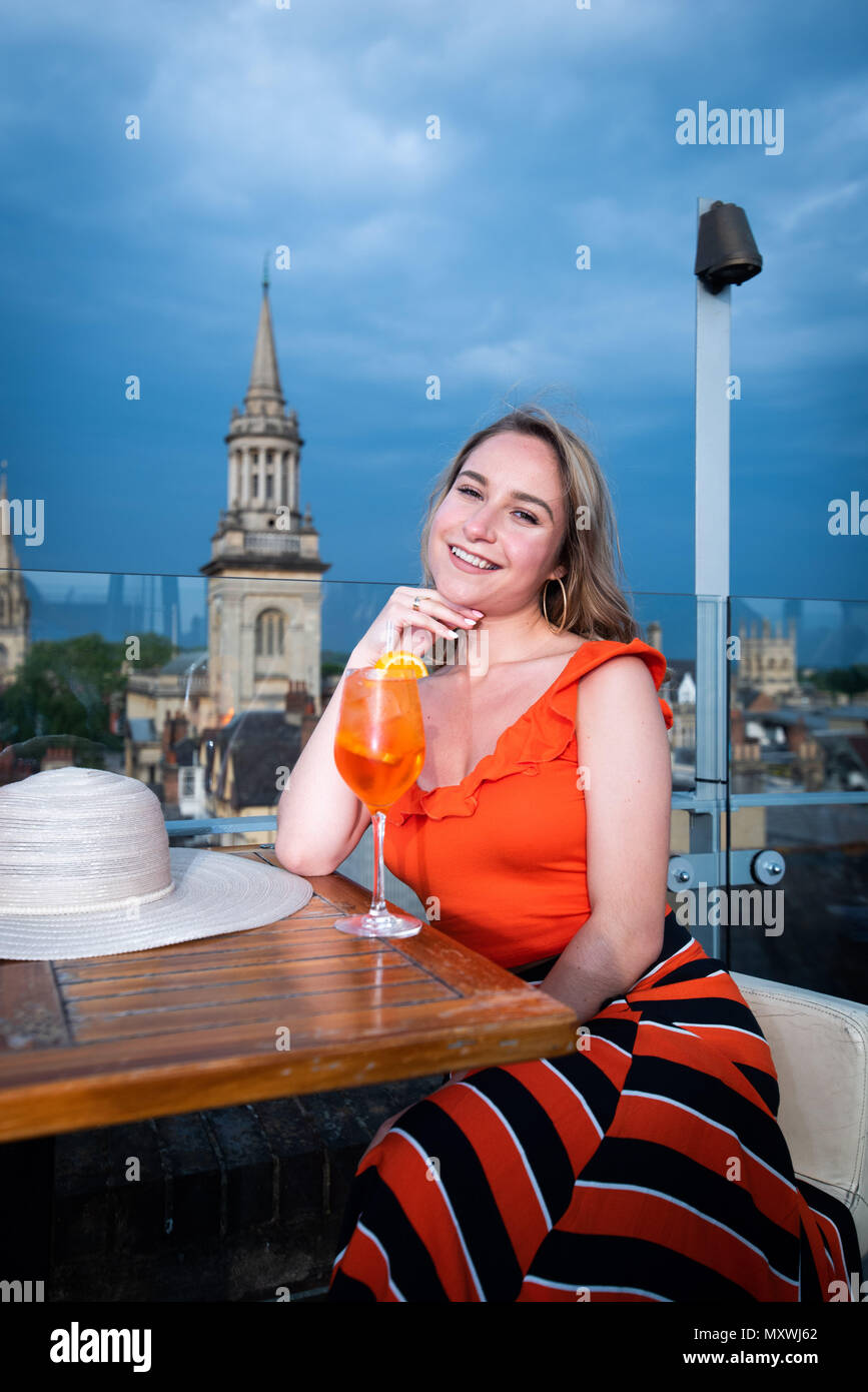 Fashion and lifestyle blogger Andreea Rasclescu at the rooftop bar in Oxford, the Varsity Club, drinking an orange glass of Aperol to match her outfit - Stock Image
