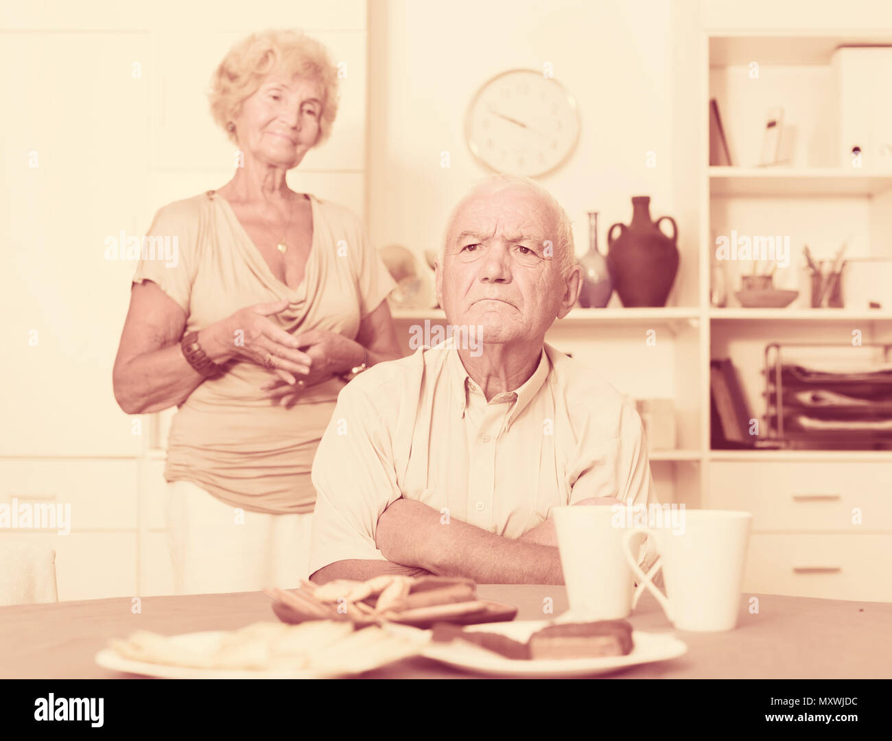 Upset mature man dont speaking after discord with woman standing behind - Stock Image