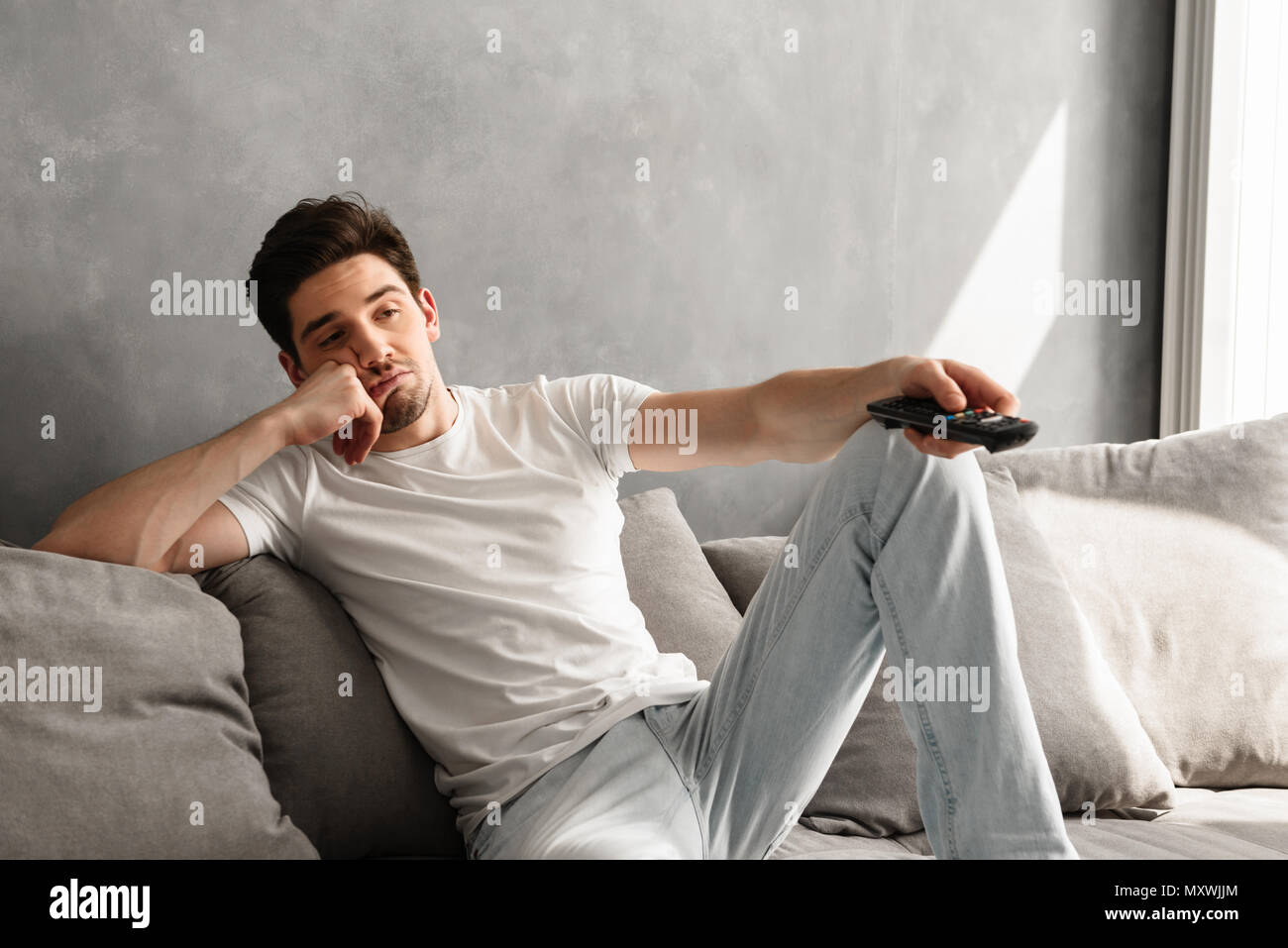 Photo of young bored man sitting on couch at home and changing TV ...