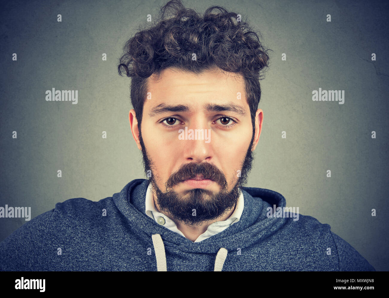 Closeup of young hipster man with curls having depression and looking sadly at camera with pity. - Stock Image