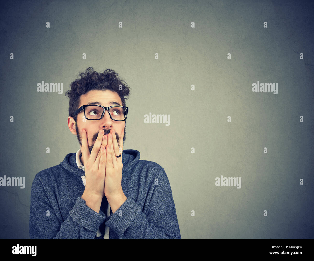 Handsome bearded man in glasses holding hands on mouth in fear and despair looking away. - Stock Image