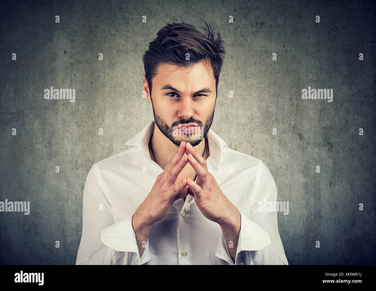 Young man holding hands together and looking at camera with thoughts of revenge and jealousy - Stock Image