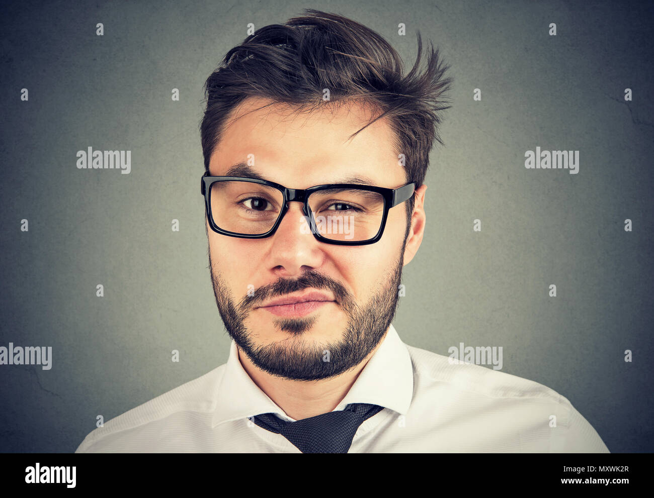 Business man in glassess looking super skeptically at camera with expression of annoyance and misunderstand - Stock Image