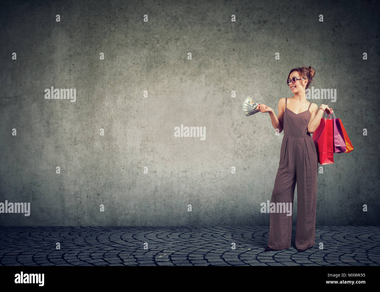 Stylish young woman holding paper bags and wasting money on shopping looking confident. - Stock Image