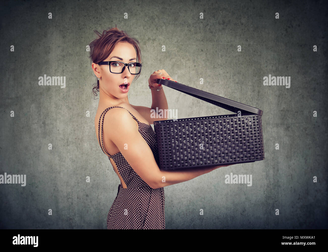 Young amazed woman opening box and looking shocked with mysterious gift inside looking at camera - Stock Image