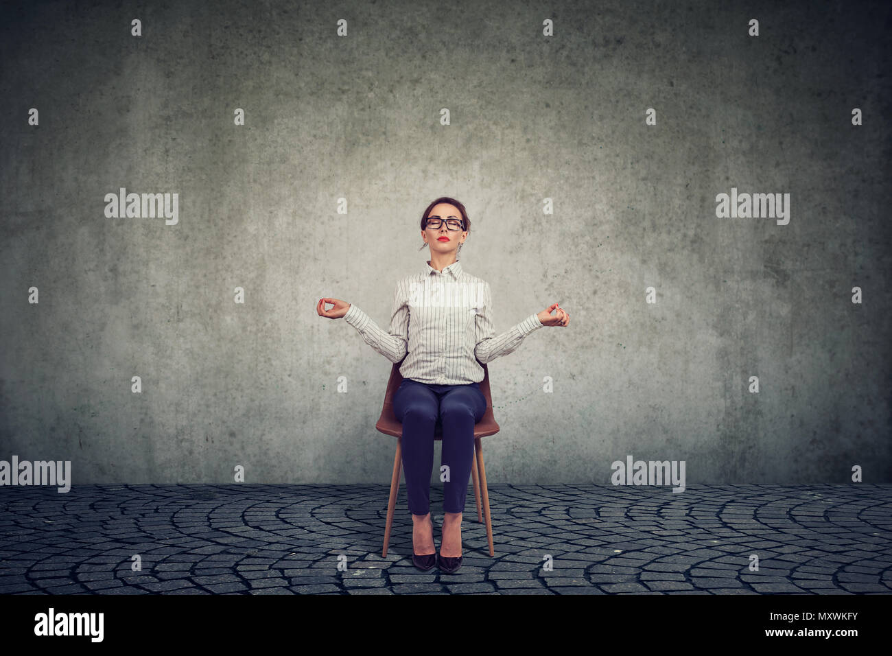 Young woman working sitting on chair in workday and meditating to conserve peace of mind at work - Stock Image