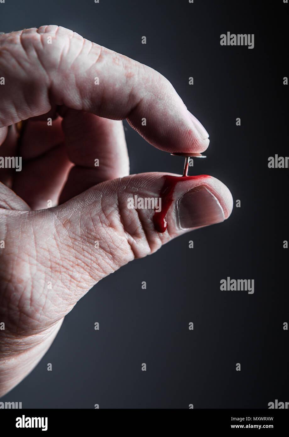 A man's hand pressing a thumbtack into his thumb Stock Photo