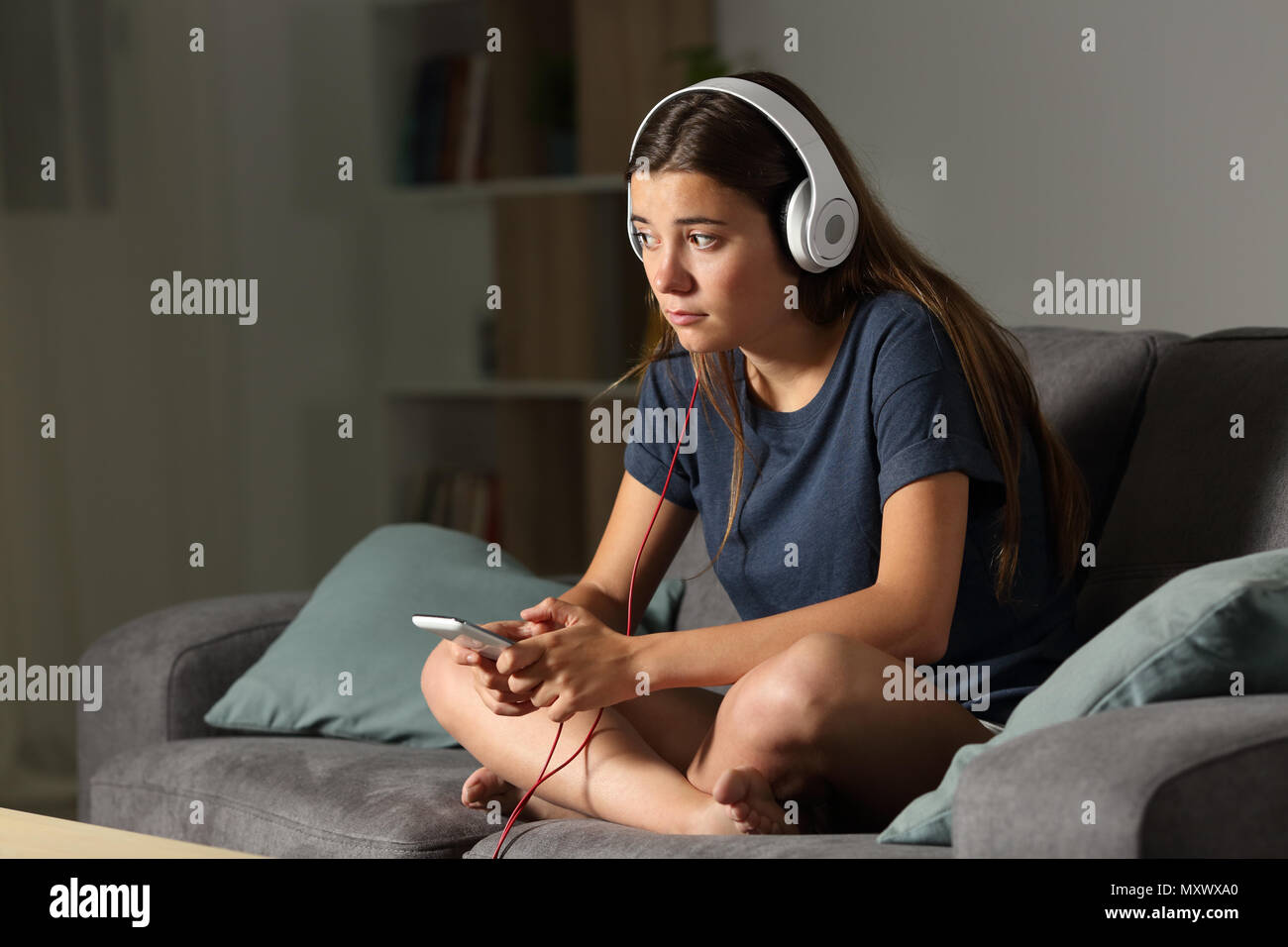 Full body portrait of a sad teen listening to music alone sitting on a couch in the living room at home