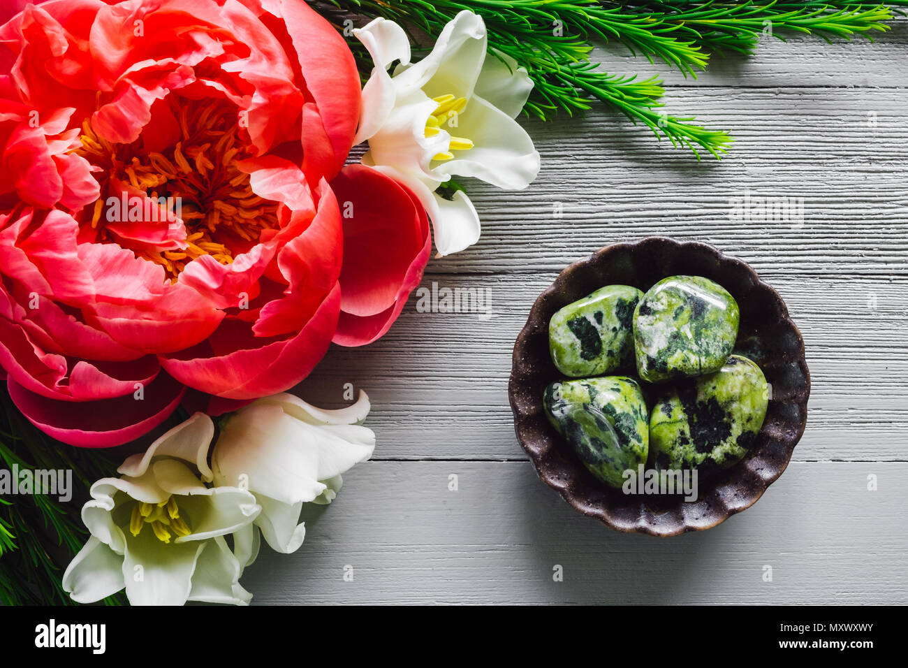 Nephrite Jade on White Table with Tulip and Peony Flowers Stock Photo