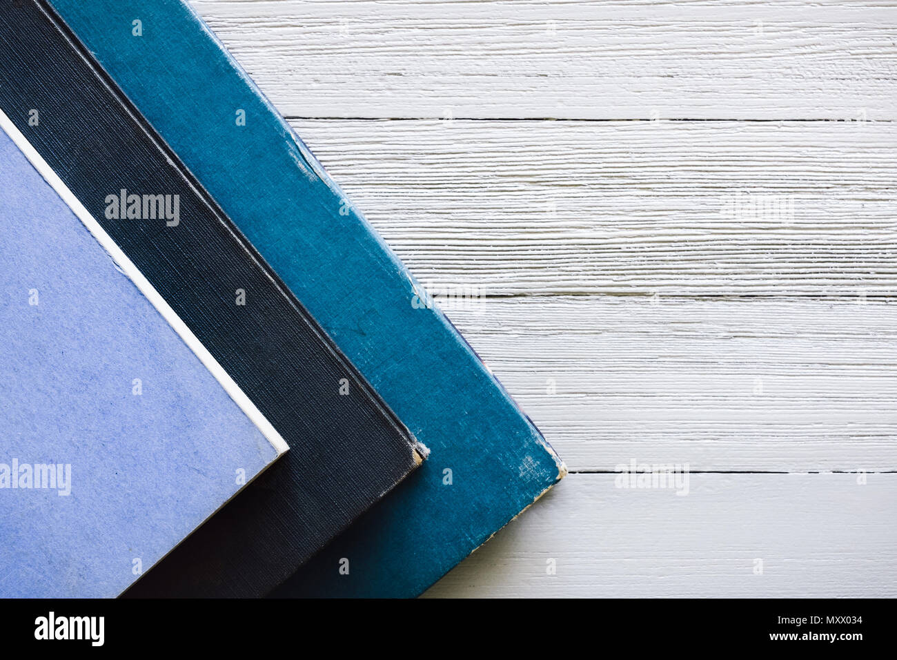 Stacked Blue Covered Books on White Table - Stock Image