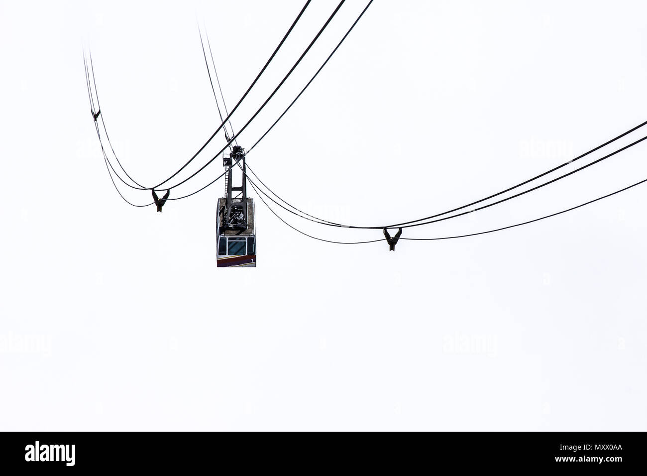 Cable car isolated on white background in foggy mountains - Stock Image