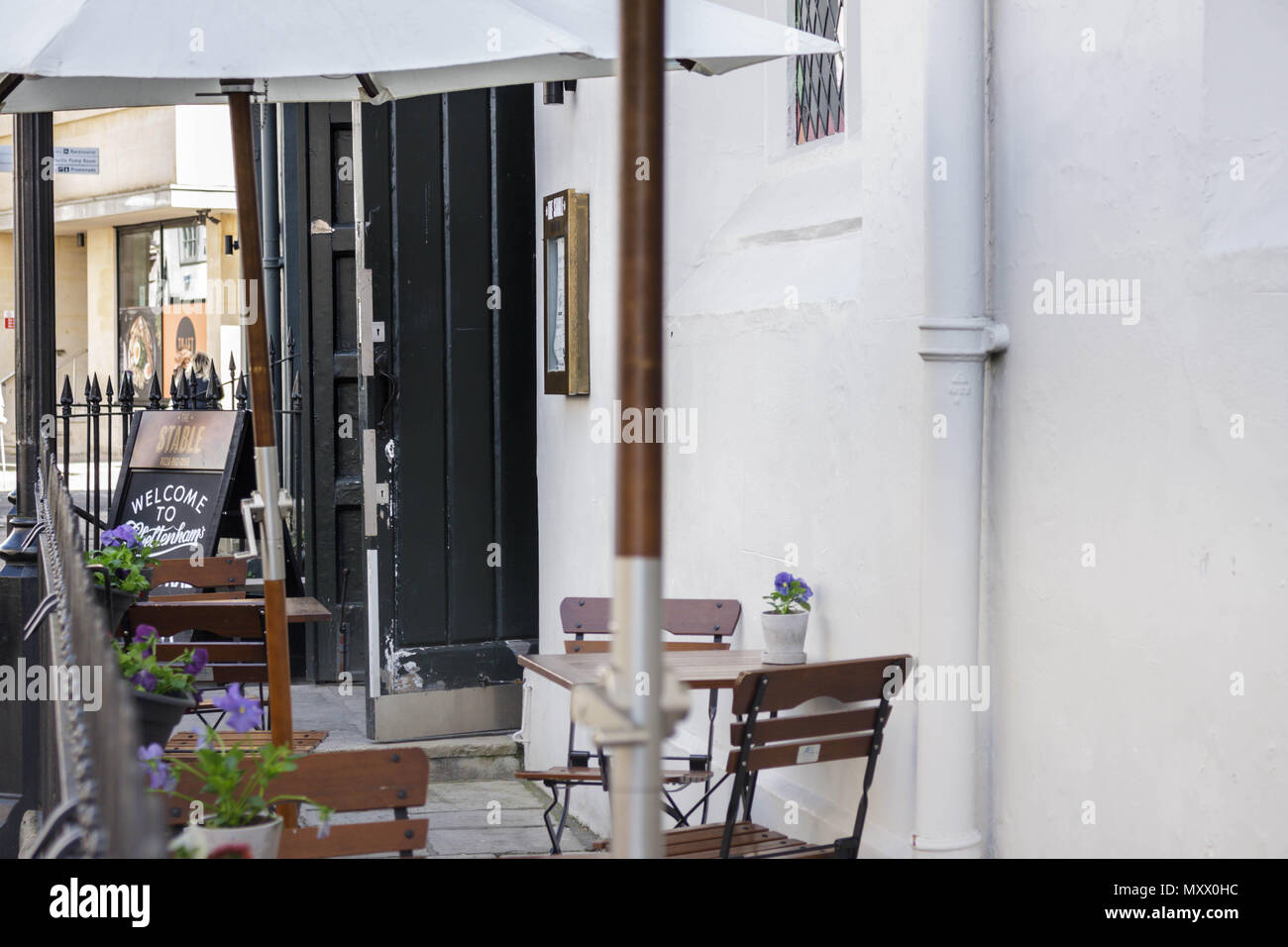 Street scene in a regency town in the UK. Image showing buildings, walls, shops, plants. Urban image. - Stock Image