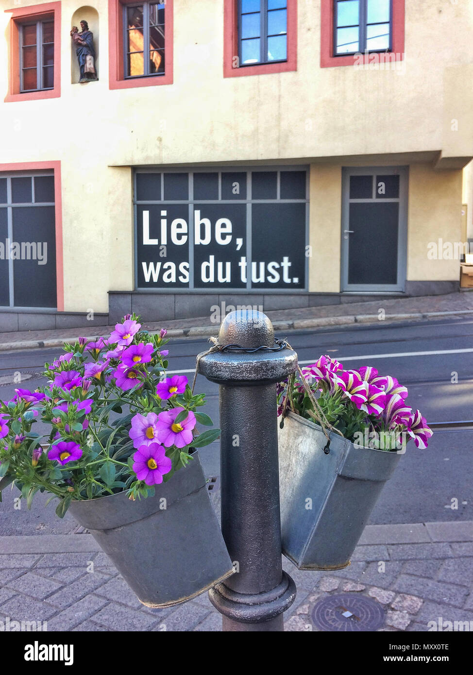 Mainz, Germany – May 15, 2017: Liebe was Du tust (love what you do) written on a house with flowers in the foreground - Stock Image