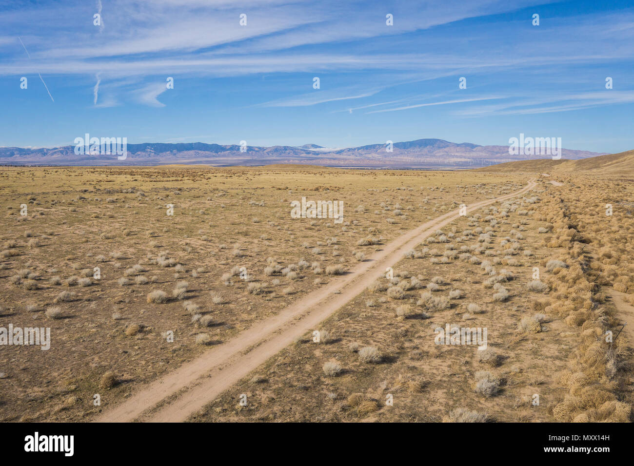 Overhead view of dirt road running alongside a wire fence in the vast dry plains of central California. Stock Photo