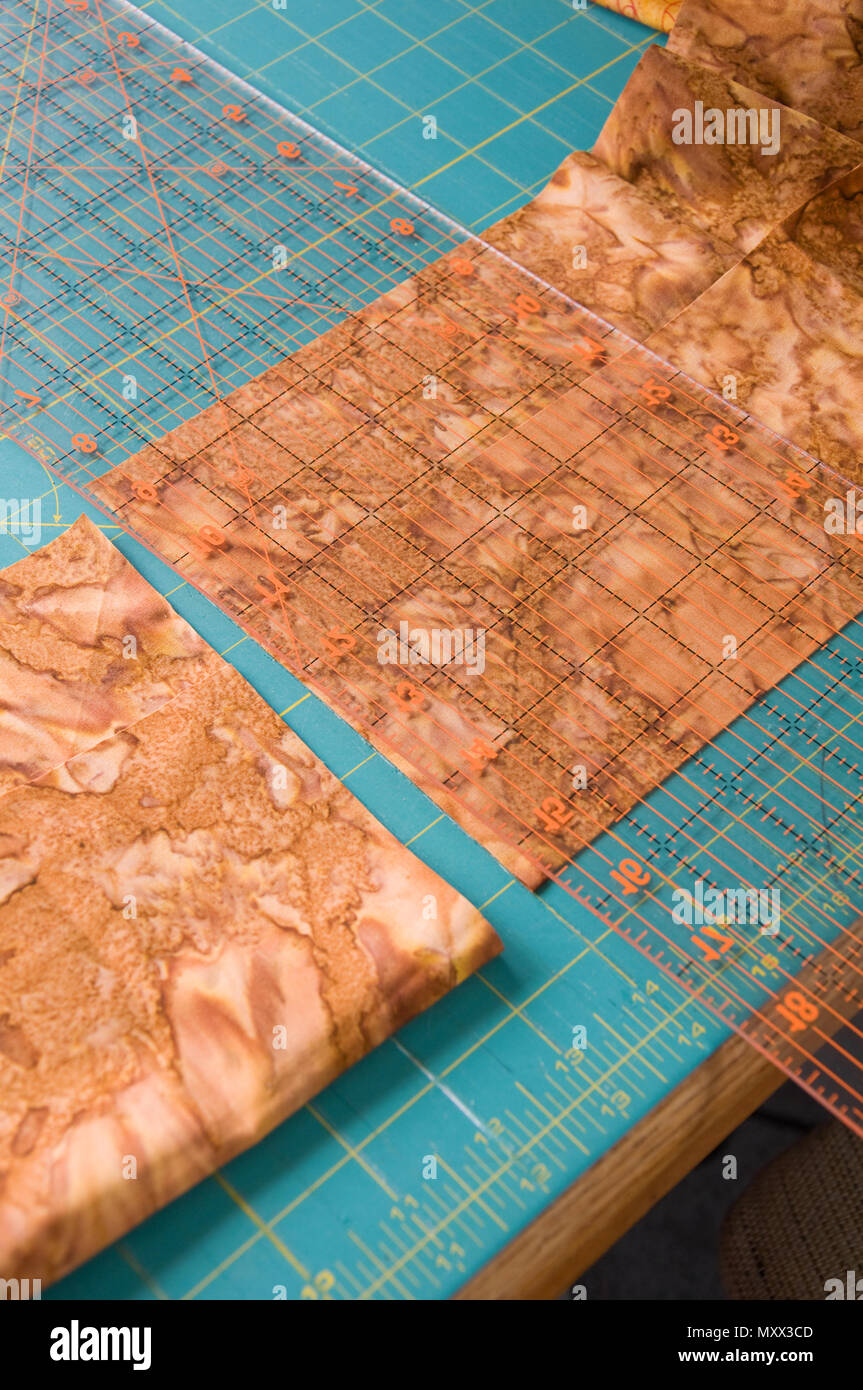 This image is a craft table of quilting supplies fabric and ruler still life about to be cut, in a vertical format. - Stock Image