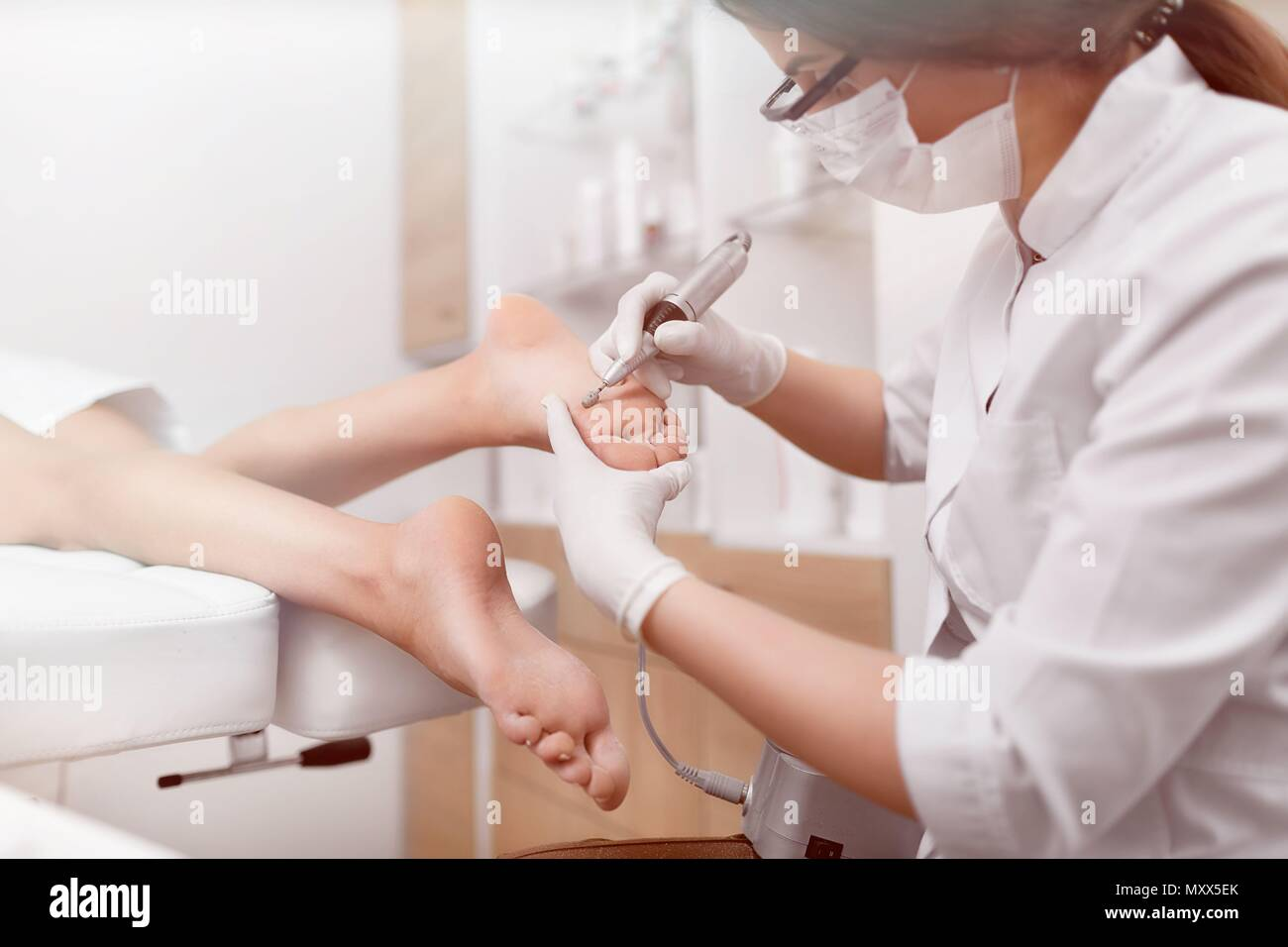 Podiatrist using special grinding equipment. - Stock Image