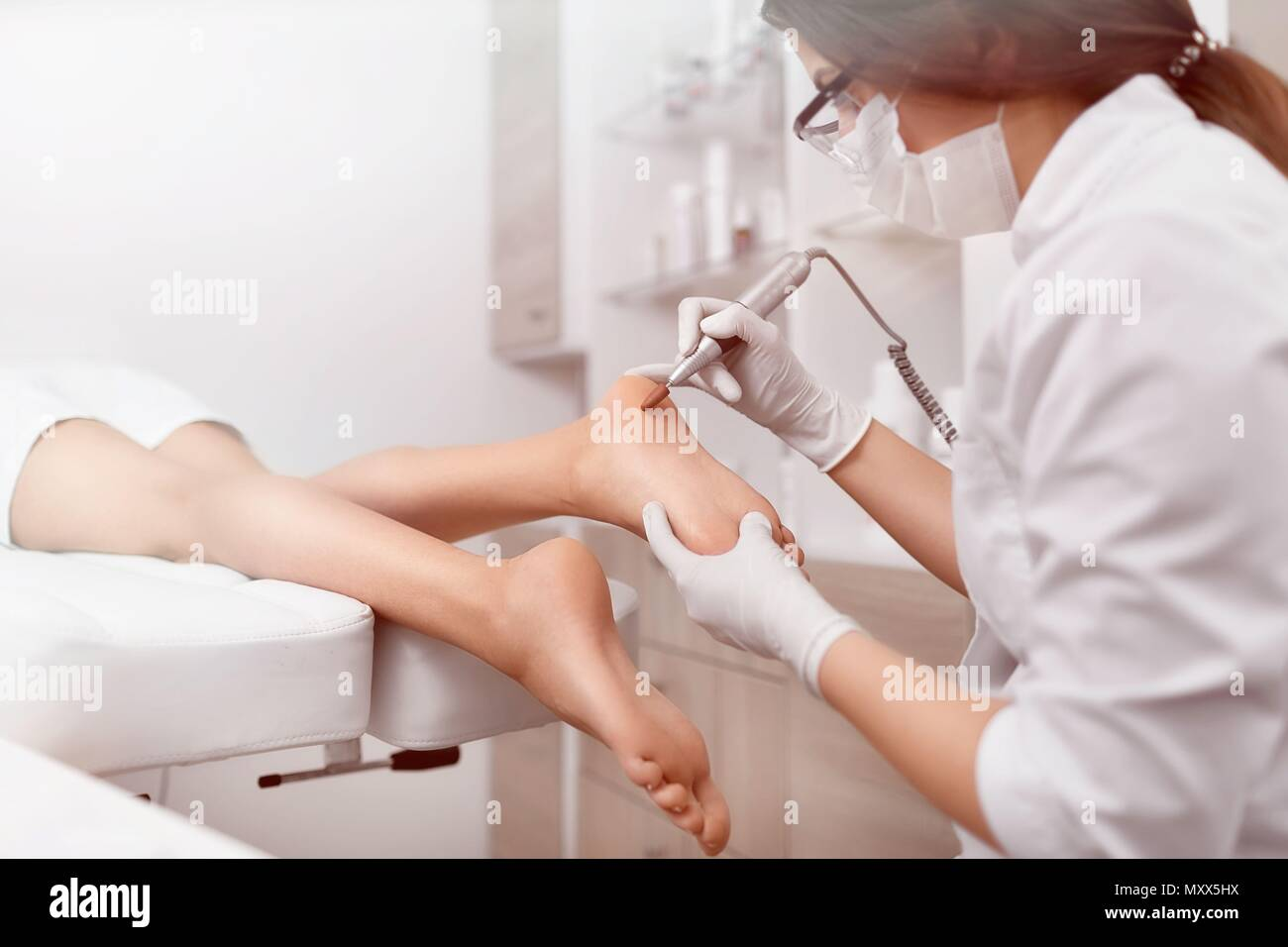 Podiatrist making procedure for client foot with special equipme - Stock Image