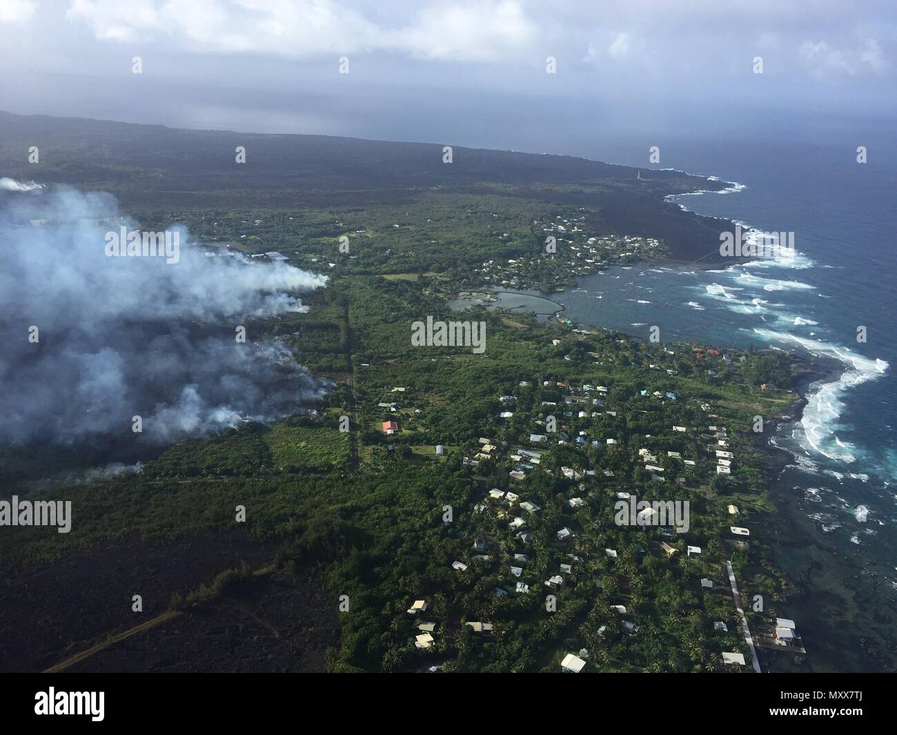 Lava flows toward the coast destroying forest and homes in the Vacationland area caused by the eruption of the Kilauea volcano June 3, 2018 in Hawaii. The recent eruption continues destroying homes, forcing evacuations and spewing lava and poison gas on the Big Island of Hawaii. - Stock Image